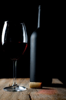 Bicchiere di vino rosso sul tavolo in legno rustico, con accanto un cavatappi e una bottiglia di vino sfocati