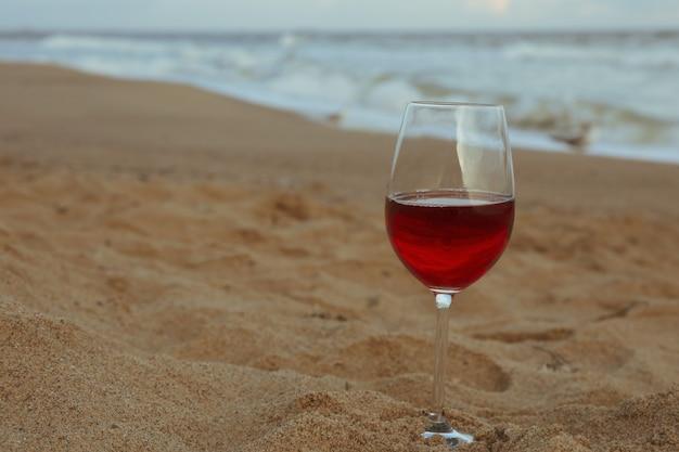 Bicchiere di vino rosso sulla spiaggia di sabbia del mare