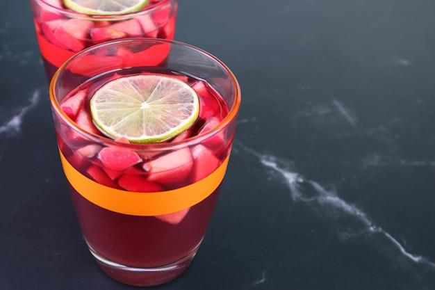Bicchiere di vino rosso sangria con un altro bicchiere sfocato sullo sfondo