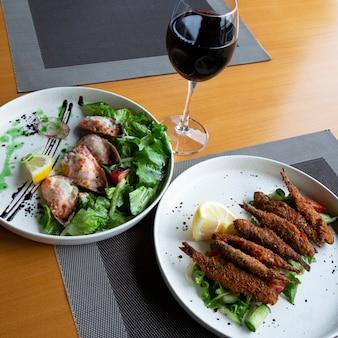 Un bicchiere di vino rosso e frutti di mare: pesce con verdure e cozze al forno al ristorante
