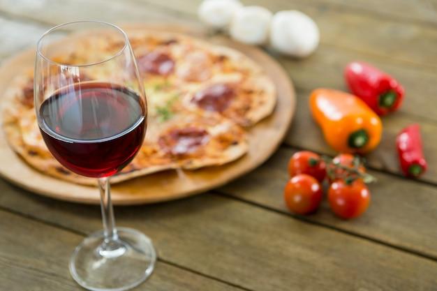 Un bicchiere di vino rosso servito con pizza italiana in background
