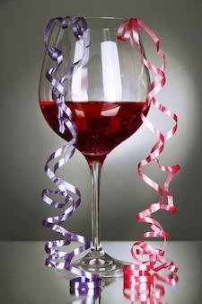 Bicchiere di vino rosso e streamer dopo la festa sul muro grigio