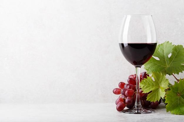 Bicchiere di vino rosso sul tavolo, uva e foglie di vite. sfondo chiaro.