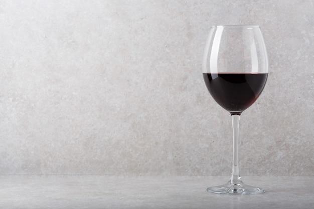 Bicchiere di vino rosso sul tavolo. sfondo chiaro