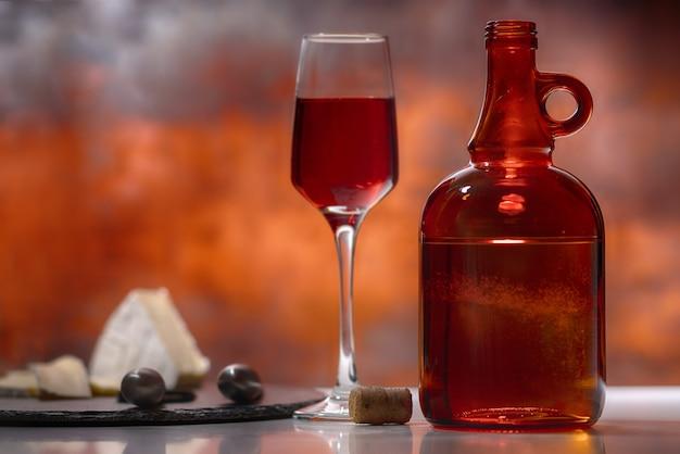 Bicchiere di vino rosso con bottiglia e tagliere di formaggi su un bancone di un bar o un pub