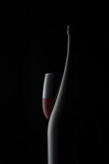 Un bicchiere di vino rosso con la bottiglia su sfondo scuro foto pubblicitaria per la produzione con ...