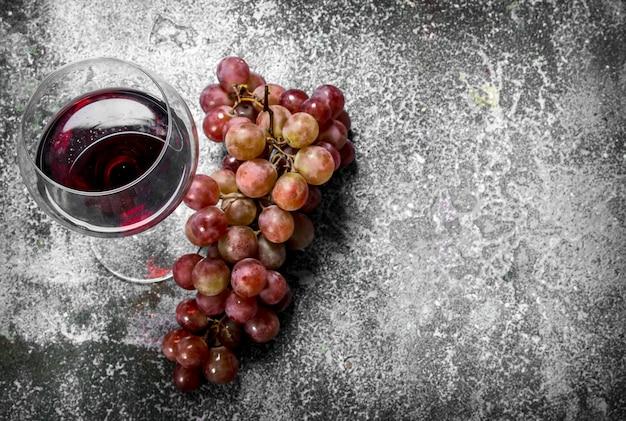 Bicchiere di vino rosso con un ramo di uva fresca. su fondo rustico.