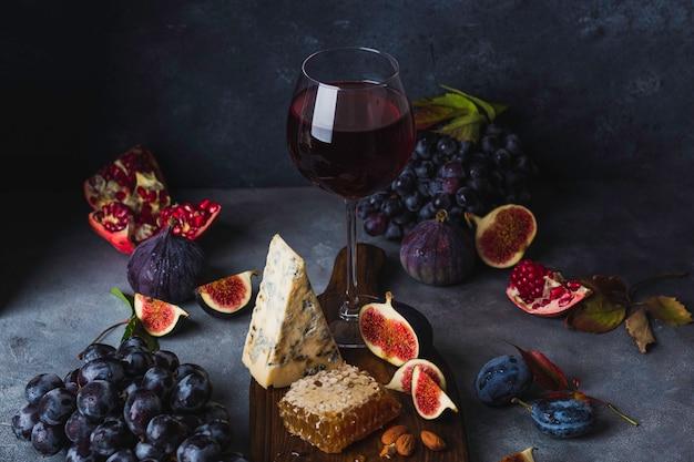 Bicchiere di vino rosso con uva, miele, formaggio dorblu e fiig