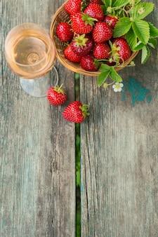 Un bicchiere di vino rosato servito con fragole fresche su fondo in legno