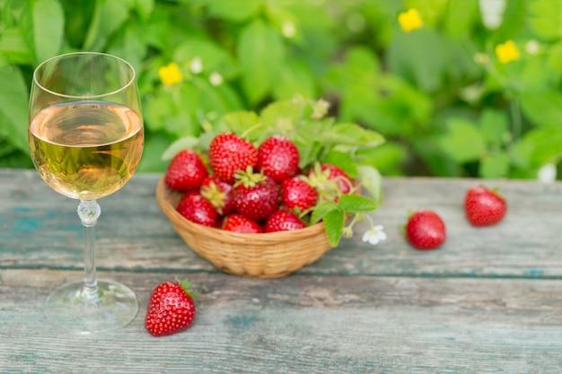 Un bicchiere di vino rosato servito con fragole fresche sulla tavola di legno