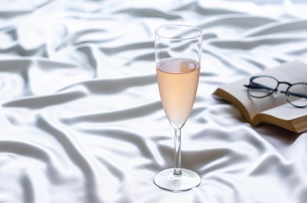 Un bicchiere di vino rosato su un panno di raso ondulato con libro e occhiali