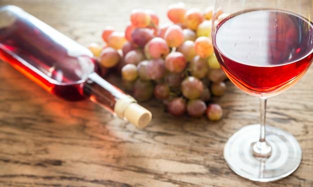 Bicchiere di vino rosato con grappolo d'uva