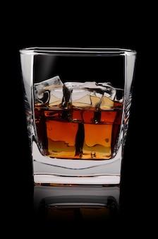 Bicchiere di scotch whisky e ghiaccio sul nero