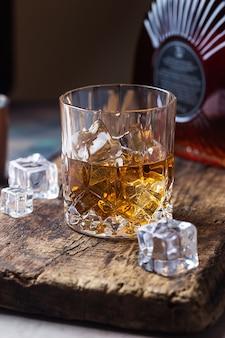 Bicchiere di whisky scozzese con cubetti di ghiaccio, bottiglia e accessori da bar in rame