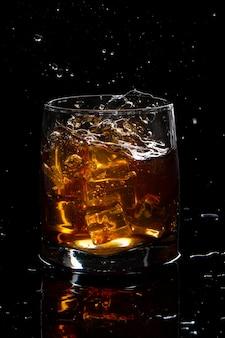 Bicchiere di whisky scozzese con spruzzata e ghiaccio su sfondo nero