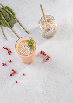 Un bicchiere di frullati a base di bacche di ribes rosso e latte di cocco con la buccia di semi di piantaggine