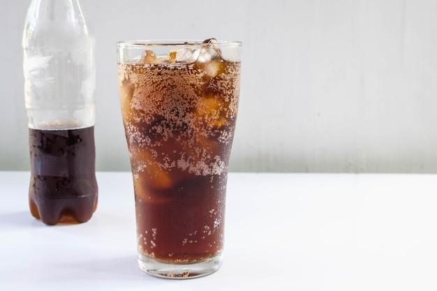 Bicchiere di bibite e bibite nere sul tavolo