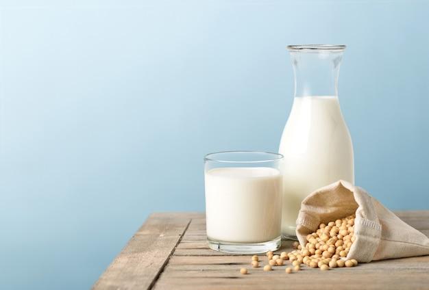 Bicchiere di latte di soia con bottiglia e semi di soia