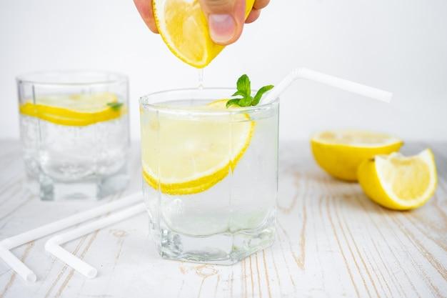 Bicchiere di soda frizzante con ghiaccio, menta e limone.