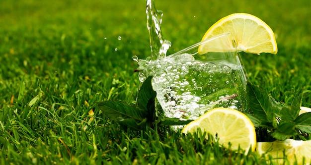 Bicchiere di acqua frizzante o limonata con limone e foglie di menta. l'acqua con spruzzi e gocce scorre in un bicchiere. bandiera.