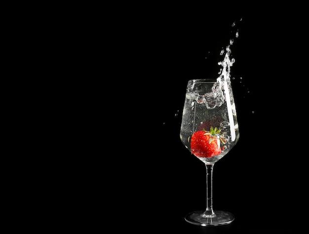 Bicchiere di spruzzi di bevanda con fragola rossa sul nero
