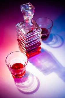 Caraffa quadrata di vetro con liquore con due bicchieri di vetro. vista dall'alto