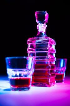 Caraffa quadrata di vetro con liquore con due bicchieri di vetro