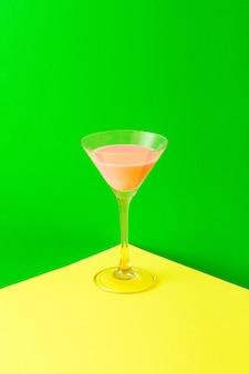 Un bicchiere in piedi sull'angolo giallo riempito con una bevanda al neon rosa su uno sfondo al neon verde. concetto minimo di festa con colori vivaci.