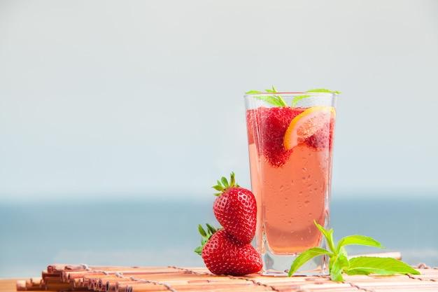 Bicchiere di limonata alla fragola con pezzi di limone alla fragola e menta fresca