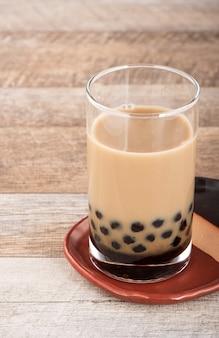 Un bicchiere di tè alle bolle di latte dolce con perle di tapioca e paglia su fondo in legno. copia spazio