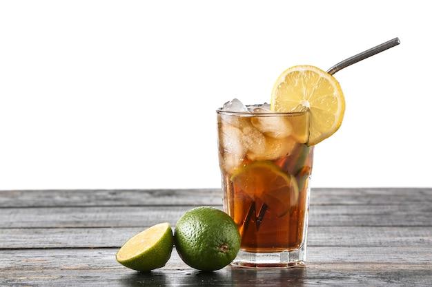 Bicchiere di gustoso cocktail cuba libre sul tavolo su sfondo bianco
