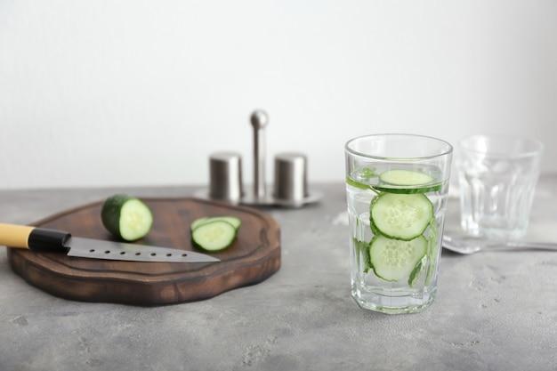 Bicchiere di gustosa acqua fresca di cetriolo con tagliere sul tavolo grigio