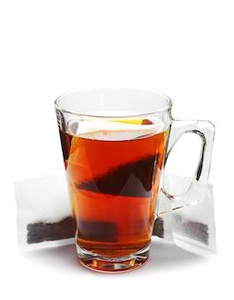Tazza da tè in vetro e bustine di tè su sfondo bianco