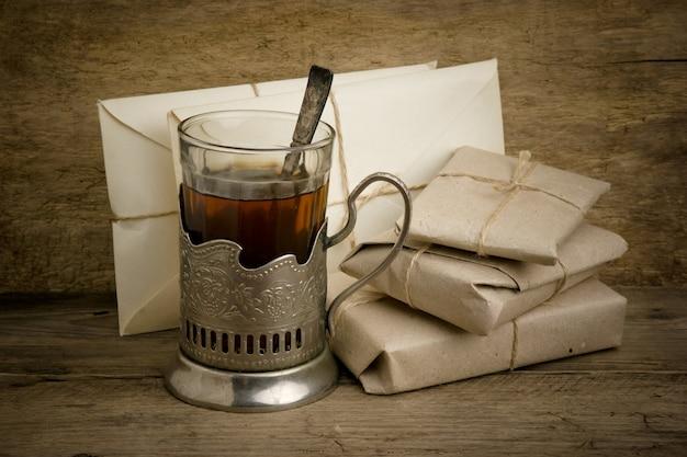 Bicchiere di tè e buste postali su fondo in legno