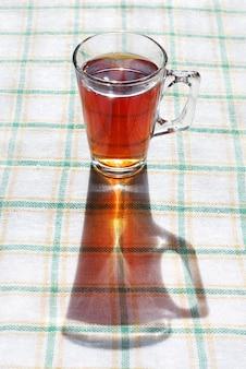 Bicchiere di tè sulla tovaglia in pieno sole