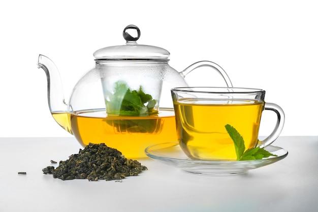 Teiera e tazza di vetro con gustoso tè alla menta su superficie bianca