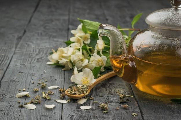 Una teiera di vetro con tè fresco fatto di petali di gelsomino su un tavolo di legno.