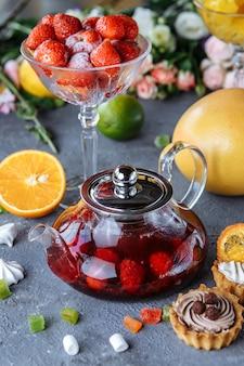Teiera in vetro con tè alla frutta lampone e menta su una superficie blu con frutta e decorazioni