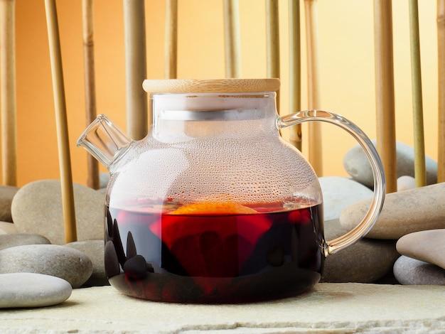 Teiera di vetro con karkade caldo del tè della bacca rossa, primo piano. tè sullo sfondo di un boschetto di bambù e pietre. concetto di tea party cinese tradizionale. giornata internazionale del tè, sfondo.
