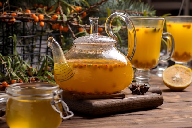 Teiera in vetro con tè all'olivello spinoso arancione. bevande calde invernali su fondo di legno marrone.