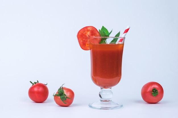Un bicchiere di succo di pomodoro e pomodori sparsi su uno sfondo bianco.