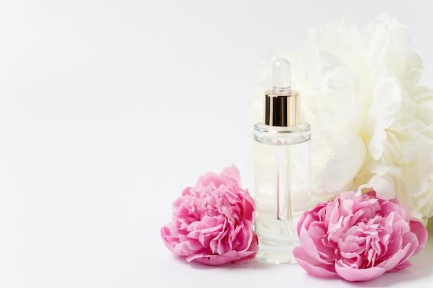 Flacone in vetro trasparente con contagocce con siero cosmetico, olio, essenza tra fiori di peonia rosa e bianchi su fondo bianco