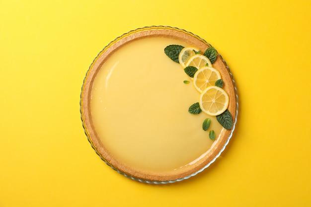 Vassoio di vetro con la crostata al limone su fondo giallo, vista superiore