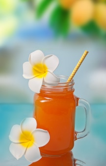 Bicchiere di tropicale esotico multifrutta succo cocktail drink con plumeria frangipani fiore per la decorazione.
