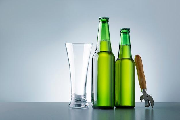 Vetro e due bottiglie di birra su un tavolo di legno scuro