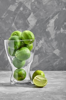 Vaso di vetro pieno di lime verdi su fondo di cemento.