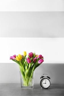 Vaso di vetro con bouquet di bellissimi tulipani su sfondo colorato