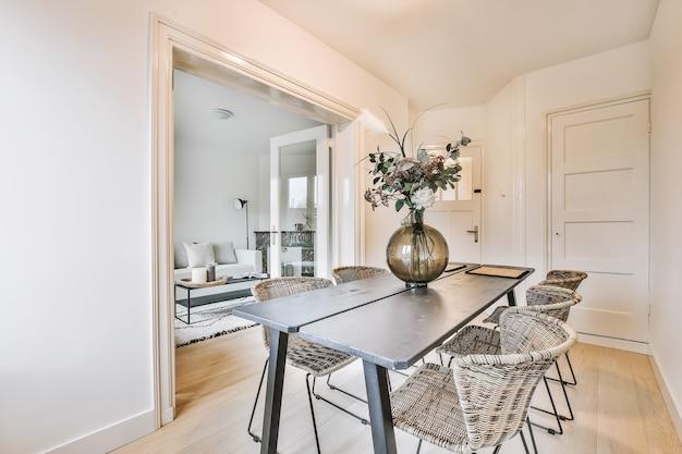 Vaso di vetro con un mazzo di fiori freschi posto sul tavolo con sedie in un'elegante sala da pranzo a casa