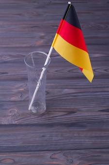 Vaso di vetro con bandiera della germania su fondo di legno grigio