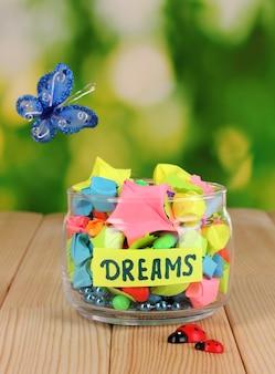 Vaso di vetro con stelle di carta con sogni su tavola di legno su sfondo naturale